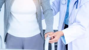 close up female doctor wearing medical mask supporting senior woman by using walker elderly patient care health care medical concept